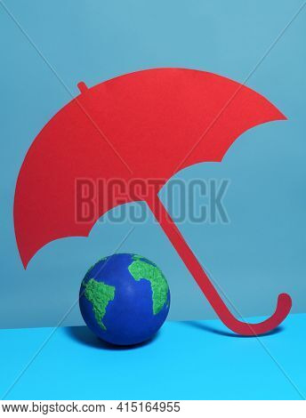 Conceptual image of planet Earth under red umbrella