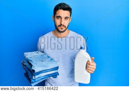 Young hispanic man holding folded jeans and detergent bottle skeptic and nervous, frowning upset because of problem. negative person.