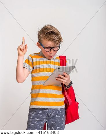 Boy Reading An E-book Instead Of Books. Caucasian 7 Years Old Boy With Tablet Computer Pointing Up W