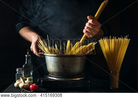 Chef Cooks Italian Pasta, On The Background Of Vegetables. Close-up Of A Cook Hand Holding Spaghetti