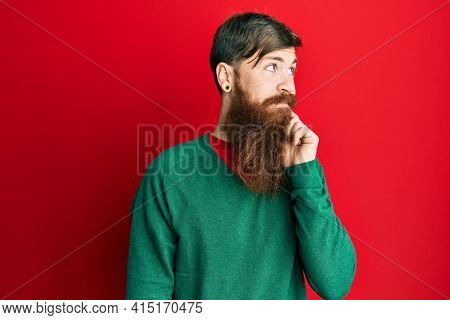 Redhead man with long beard wearing casual clothes thinking concentrated about doubt with finger on chin and looking up wondering