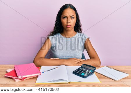 Young african american girl accountant working at the office skeptic and nervous, frowning upset because of problem. negative person.