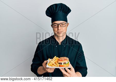 Handsome young man chef holding burger with fries relaxed with serious expression on face. simple and natural looking at the camera.