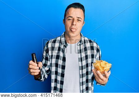 Handsome young man drinking a pint of beer holding chips sticking tongue out happy with funny expression.
