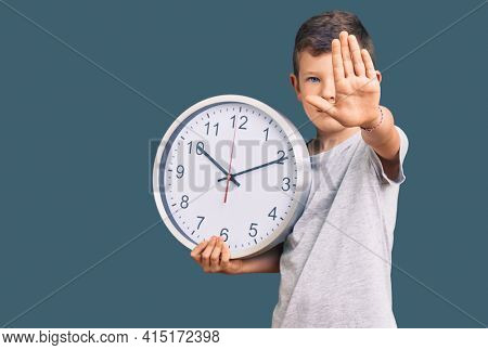 Cute blond kid holding big clock with open hand doing stop sign with serious and confident expression, defense gesture