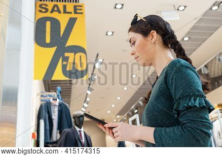 A Young Woman Emotionally Communicates On The Phone. In The Background, There Is A Store And Posters