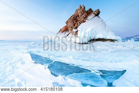 Rock On The Frozen Baikal Lake In Winter. Snow And Ice On The Surface Of The Lake. Baikal, Siberia,