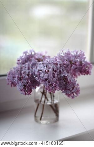 Lilac flowers bouquet close up. Bouquet of purple spring flowers on window. Bouquet of lilac in glass vase. Lilac isolated on white background