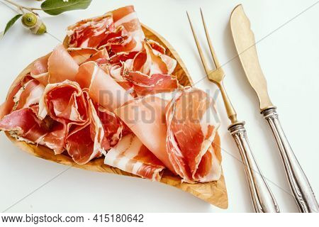 Thin Slices Of Jamon Are Laid Out On A Wooden Board Made Of Olive Wood. Close-up Of A Thin Slice Of