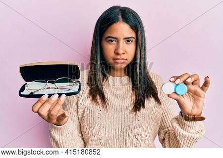 Young latin girl holding glasses and contact lenses skeptic and nervous, frowning upset because of problem. negative person.
