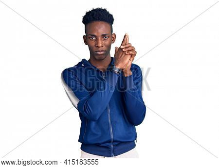 Young african american man wearing sportswear holding symbolic gun with hand gesture, playing killing shooting weapons, angry face