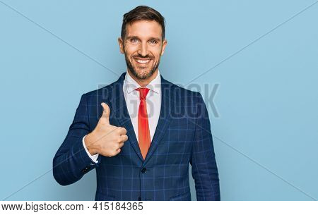 Handsome man with beard wearing business suit and tie doing happy thumbs up gesture with hand. approving expression looking at the camera showing success.