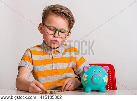 Portrait Of Smart Cute Little Boy With Piggy Bank. Portrait Of A Little Boy Take Money From Moneybox