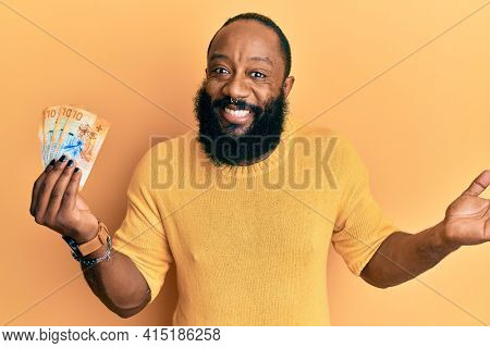 Young african american man holding 10 swiss franc banknotes celebrating achievement with happy smile and winner expression with raised hand