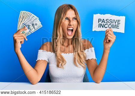 Beautiful blonde young woman holding dollars and passive income text angry and mad screaming frustrated and furious, shouting with anger looking up.