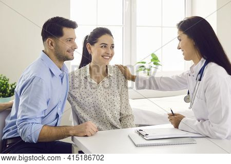 Female Doctor Consulting Young Couple Patients In Fertility Clinic About Ivf Or Iui.