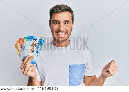 Handsome caucasian man holding swiss franc banknotes screaming proud, celebrating victory and success very excited with raised arm
