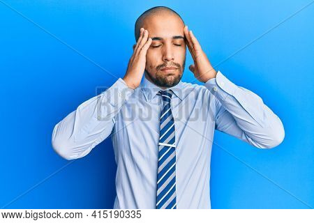 Hispanic adult man wearing business shirt and tie with hand on head, headache because stress. suffering migraine.