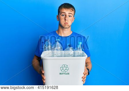 Young caucasian man holding recycling wastebasket with plastic bottles puffing cheeks with funny face. mouth inflated with air, catching air.