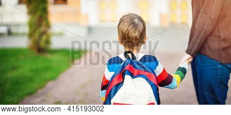 Child With Rucksack And With Mother In Front Of A School Building. Concept Of Motherhood And Beginni