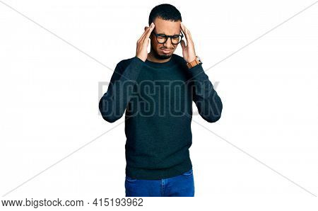 Young african american man wearing casual clothes and glasses with hand on head for pain in head because stress. suffering migraine.