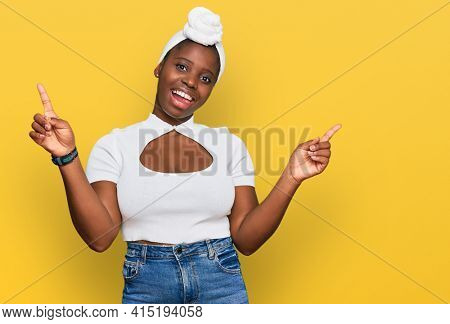Young african woman with turban wearing hair turban over isolated background smiling confident pointing with fingers to different directions. copy space for advertisement