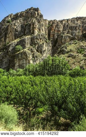Rocks Of Large Basalt Rocks Next To Peach Trees On The Road Leading To The City Of Yeghegnadzor In A