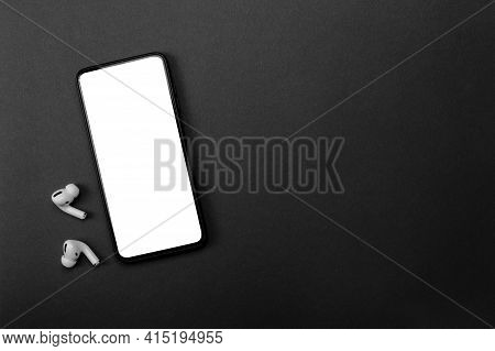 Mobile Phone With Empty Screen And Earphones On Black Surface. Wireless Earphones, Mobile Phone On B