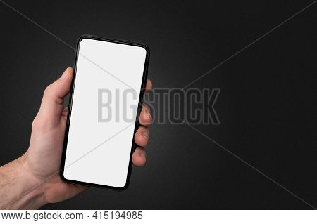 Man Hand Holding The Black Cell Phone Smartphone With Blank White Screen And Modern Frame Less Desig