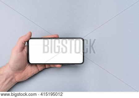 Mockup Cell Phone. Male Hand Holding Phone Horizontally With Blank White Screen. Grey Table Backgrou