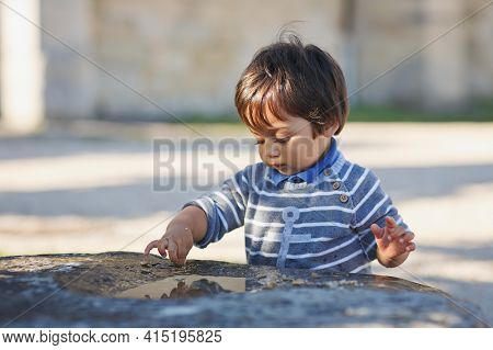 Portrait Of A Little Eastern Handsome Baby Boy Playing Outdoor In The Park. Arabian Child Fun On The