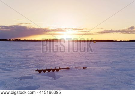 Winter Landscape, Winter Sports. Silhouettes Of Fishermen On A Winter Lake At Sunset Fishing.