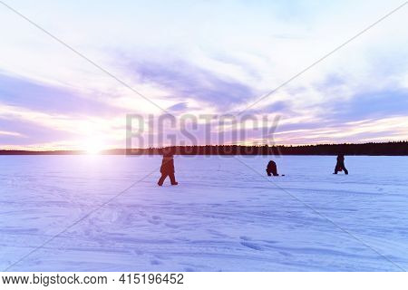 Silhouettes Of Fishermen On A Winter Lake At Sunset Fishing. Winter Landscape, Winter Sports