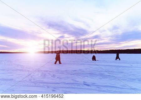 Silhouettes Of Fishermen On A Winter Lake At Sunset Fishing. Winter Landscape, Winter Sports
