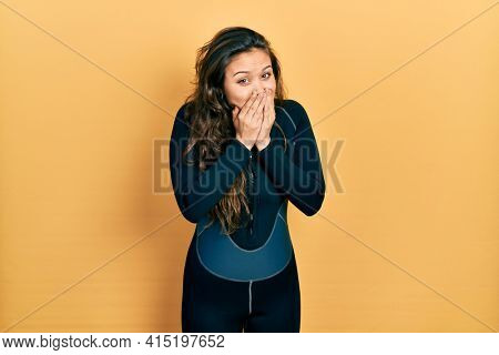 Young hispanic girl wearing diver neoprene uniform laughing and embarrassed giggle covering mouth with hands, gossip and scandal concept