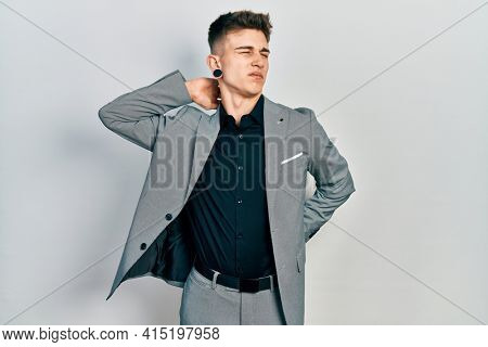 Young caucasian boy with ears dilation wearing business jacket suffering of neck ache injury, touching neck with hand, muscular pain
