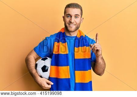 Young caucasian man football hooligan cheering game holding ball surprised with an idea or question pointing finger with happy face, number one