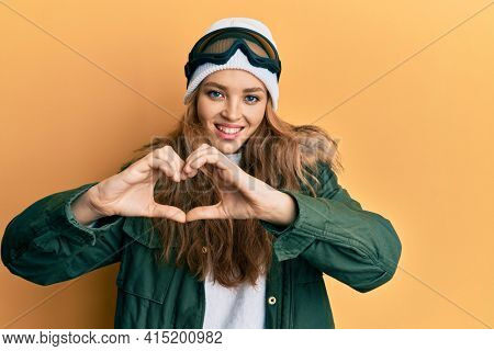 Beautiful blonde caucasian woman wearing snow wear and sky glasses smiling in love showing heart symbol and shape with hands. romantic concept.
