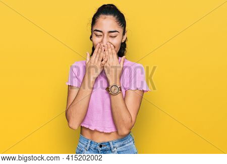Hispanic teenager girl with dental braces wearing casual clothes laughing and embarrassed giggle covering mouth with hands, gossip and scandal concept