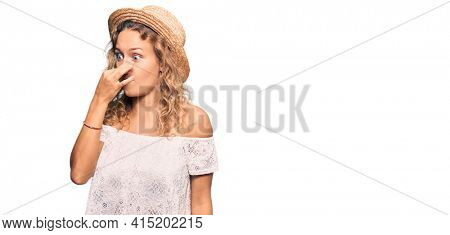 Beautiful caucasian woman wearing summer hat smelling something stinky and disgusting, intolerable smell, holding breath with fingers on nose. bad smell