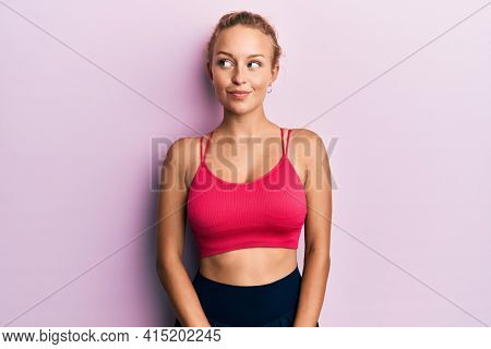 Beautiful caucasian woman wearing sportswear smiling looking to the side and staring away thinking.