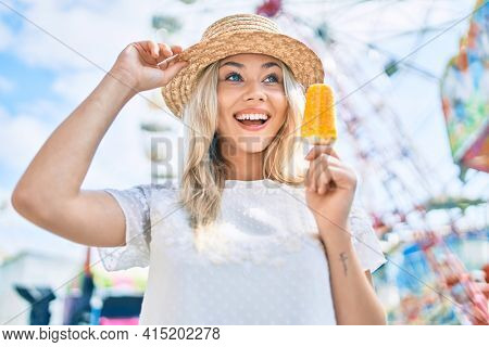Young caucasian tourist girl smiling happy and eating ice cream at fairground.