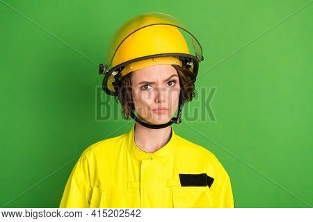 Photo Of Young Woman Firefighter Ucertain Unsure Hesitate Wear Protection Helmet Isolated Over Green