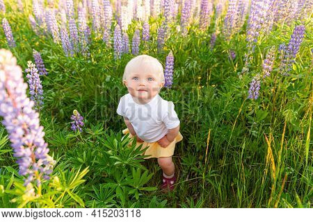 Happy Little Girl Smiling Outdoor. Beautiful Blond Young Baby Girl Resting On Summer Field With Bloo