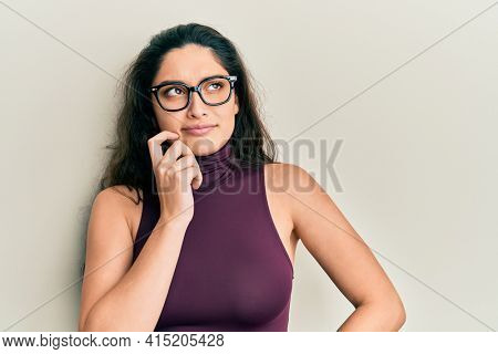 Beautiful middle eastern woman wearing casual clothes and glasses thinking concentrated about doubt with finger on chin and looking up wondering