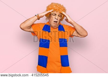 Senior hispanic man football hooligan cheering game suffering from headache desperate and stressed because pain and migraine. hands on head.