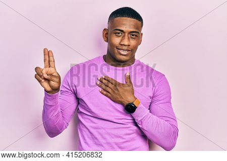 Young black man wearing casual pink sweater smiling swearing with hand on chest and fingers up, making a loyalty promise oath