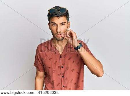 Young handsome man wearing casual summer clothes mouth and lips shut as zip with fingers. secret and silent, taboo talking