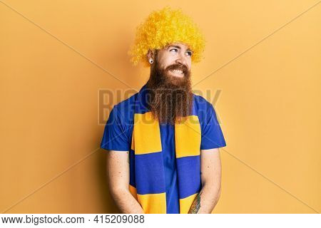 Redhead man with long beard football hooligan cheering game wearing funny wig looking away to side with smile on face, natural expression. laughing confident.