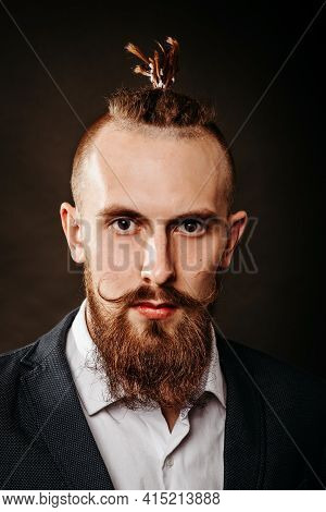 Portrait Of A Young Bearded Brutal Hipster Man, With A Long Mustache In The Studio On A Dark Backgro